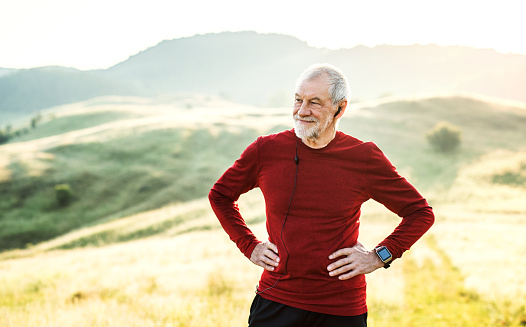 A portrait of an active senior man with earphones outdoors in nature. Copy space. - gettyimageskorea