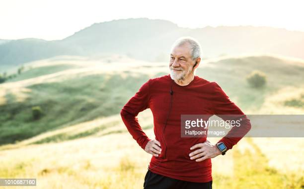 a portrait of an active senior man with earphones outdoors in nature. copy space. - active lifestyle stock pictures, royalty-free photos & images