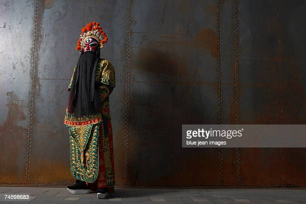 portrait of an actor dressed as a traditional beijing opera army general posing in front of an industrial rusted steel wall. - beijing opera stock photos and pictures