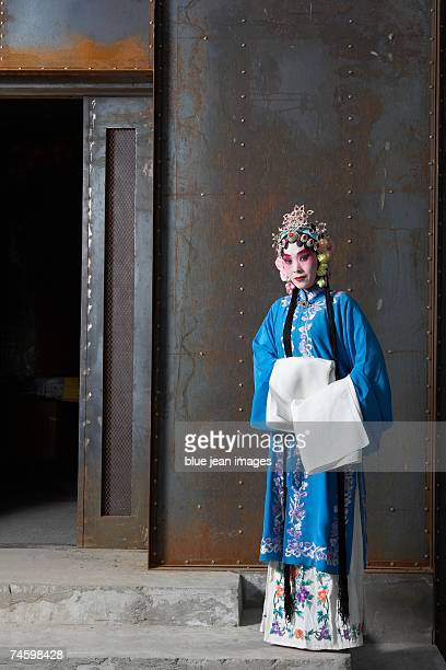 Portrait of an actress dressed as a traditional Chinese princess posing in front of a nightclub entrance.