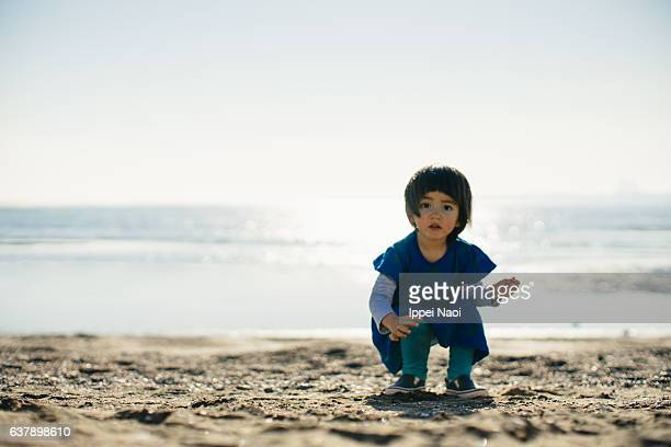 Portrait of an adorable little girl beachcombing in winter