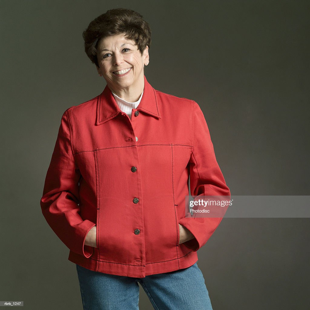 portrait of an adult caucasian brunette woman in a red coat as she smiles : Photo