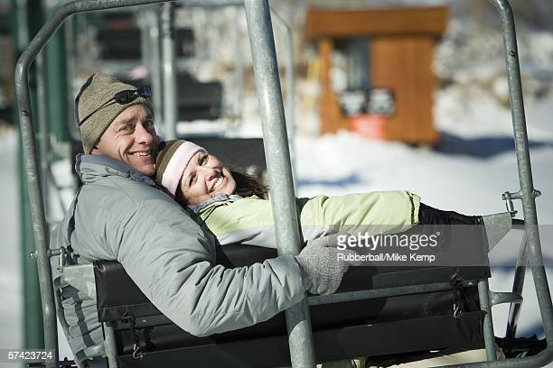 Portrait of an adult couple sitting on a ski lift