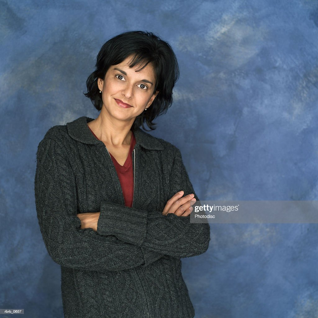 portrait of an adult ethnic woman in a grey sweater as she folds her arms and smiles : Stockfoto