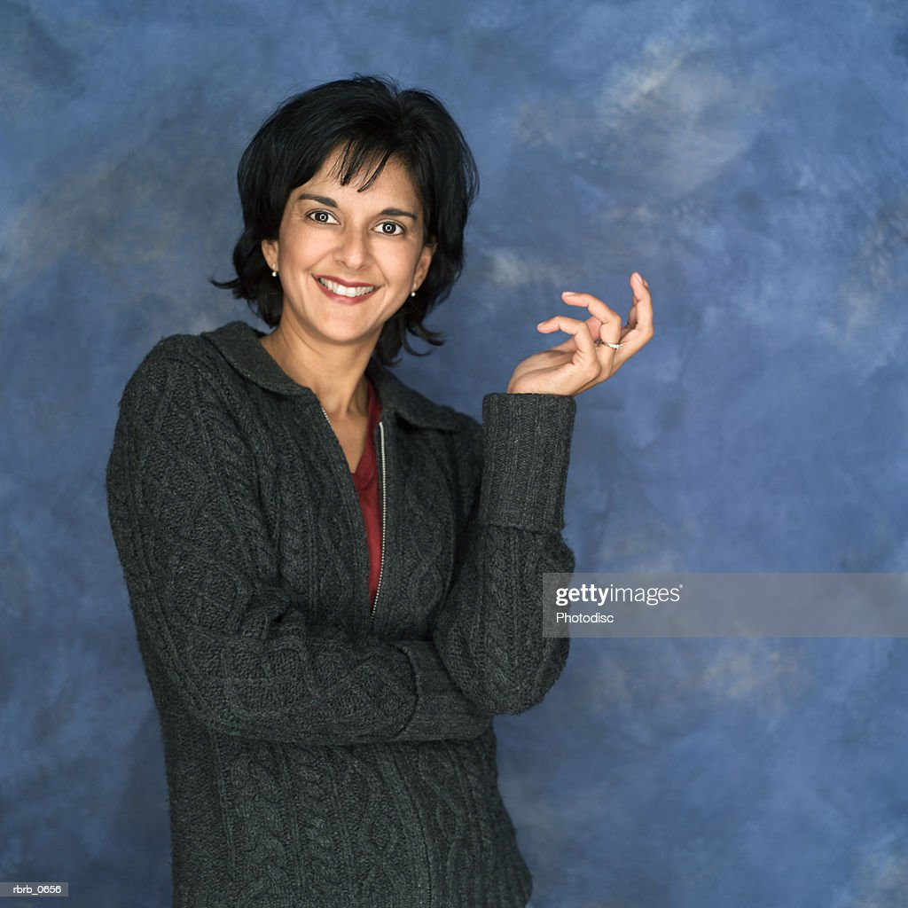 portrait of an adult ethnic woman in a grey sweater as she gestures and smiles : Stock Photo