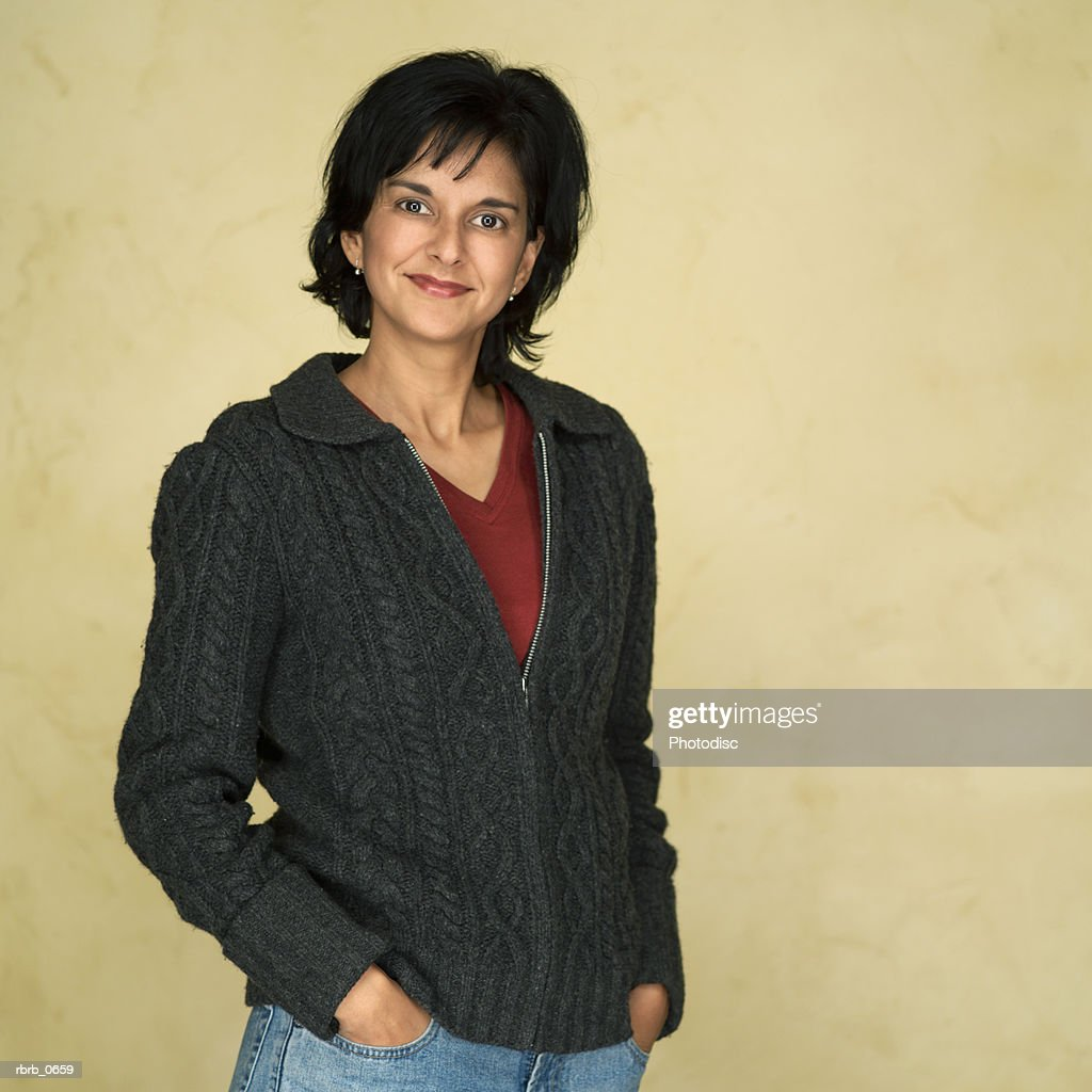 portrait of an adult ethnic woman in a grey sweater as she puts her hands in her pockets and smiles : Stockfoto