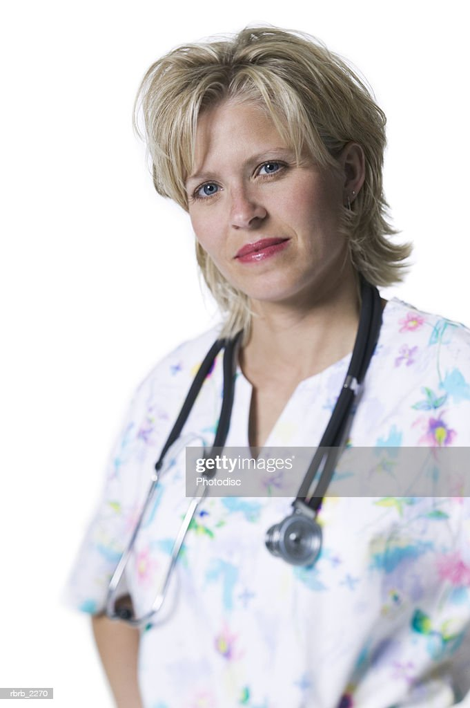 portrait of an adult female nurse in printed scrubs as she looks at the camera : Foto de stock