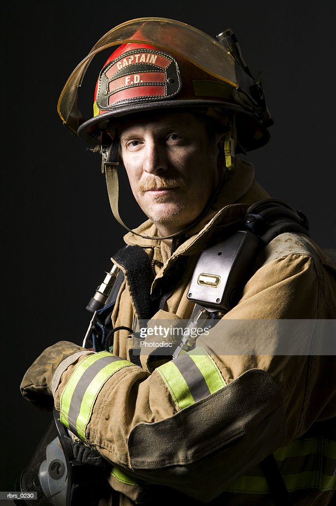 portrait of an adult fireman in his fire fighting gear as he folds his arms and looks at the camera : Foto de stock