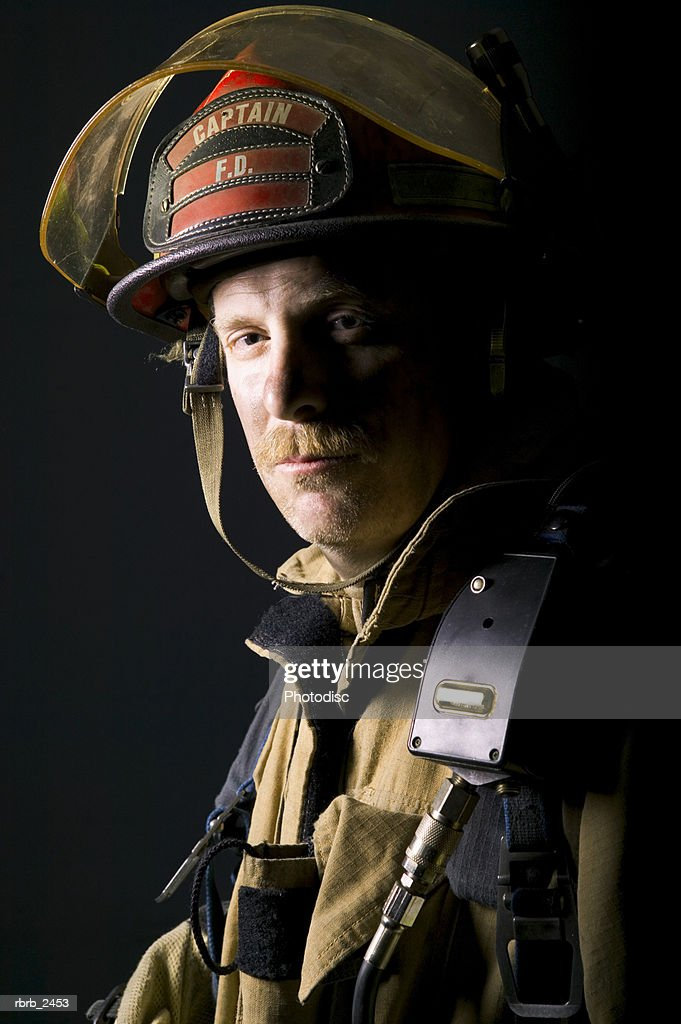 portrait of an adult male fireman as he glares at the camera : Foto de stock