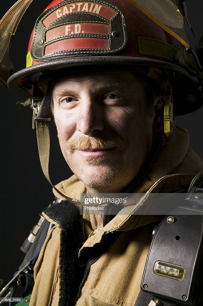 portrait of an adult male fireman as he smiles at the camera : Foto de stock