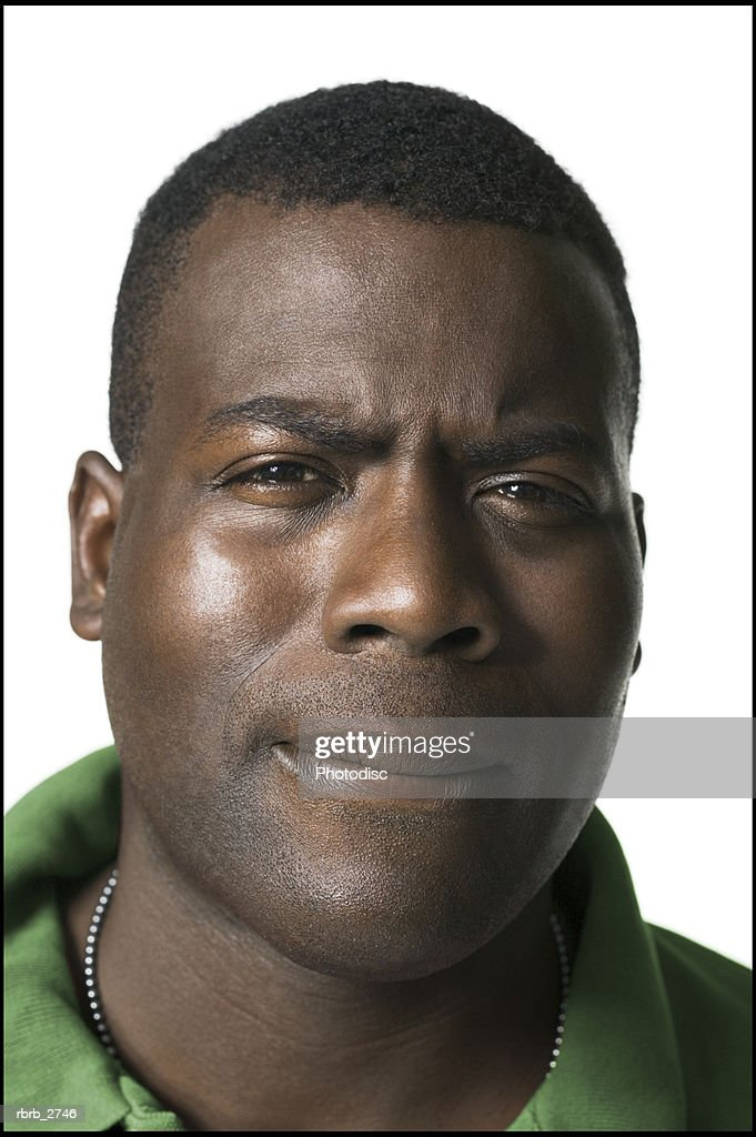 portrait of an adult male in a green shirt as he squints and frowns at the camera : Foto de stock