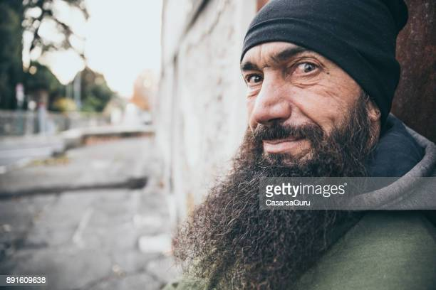 portrait of an adult man with long beard standing on city street - evil stock photos and pictures
