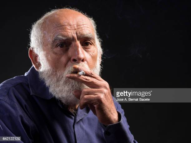 Portrait of an adult man with white beard addict to the tobacco smoking a cigarette