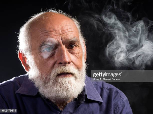 Portrait of an adult man with white beard surrounded with smoke, passive Smoker in an environment of smoke