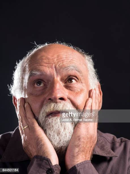 Portrait of an adult man with white beard With the hands on the head with gesture of surprise