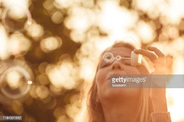 portret van een volwassen vrouw blazen bubbels tijdens zonsondergang - sepiakleurig stockfoto's en -beelden