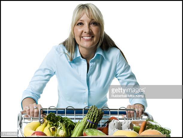 Portrait of an adult woman holding a shopping cart of vegetables and smiling