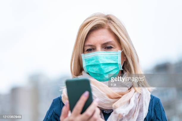 portrait of an adult woman wearing a protective face mask and using a mobile phone outdoors - obscured face stock pictures, royalty-free photos & images