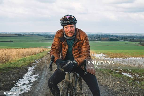 portrait of an adventure cyclist on dirt track - only men stock pictures, royalty-free photos & images