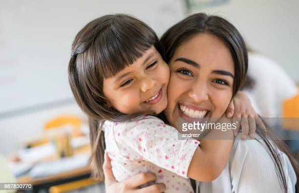 Portrait of an affectionate girl hugging her teacher at school