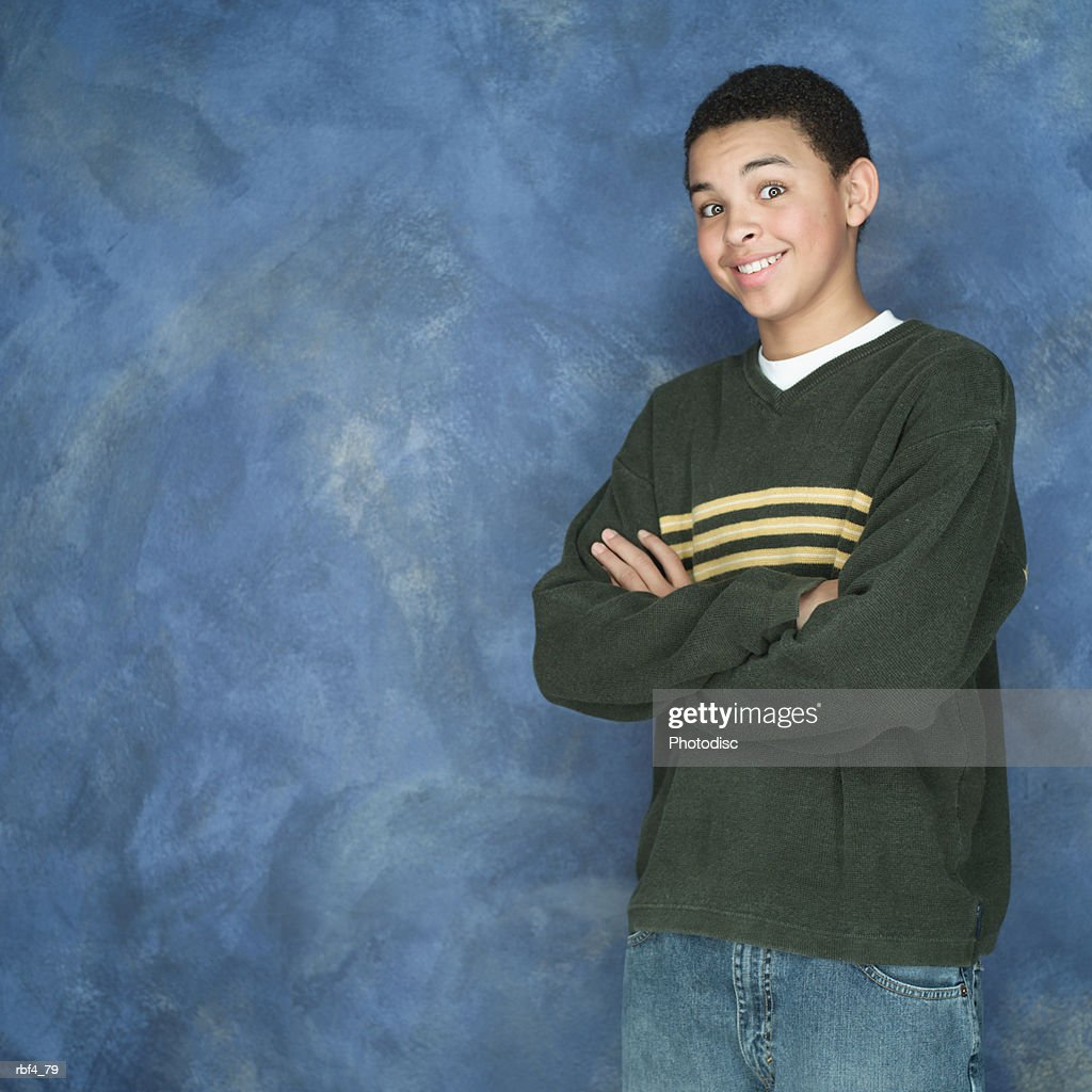 portrait of an african american boy in green sweater as he folds his arms and smiles : Stockfoto