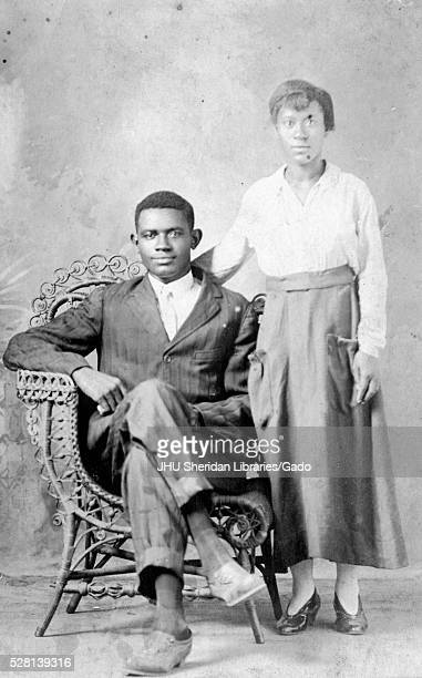 Portrait of an African American couple the man is wearing a darkcolored suit and is sitting in a wicker chair with his legs crossed the woman is...