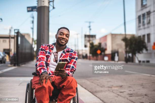portrait of an african american disabled men in a wheelchair using smart phone outdoors - wheelchair stock pictures, royalty-free photos & images