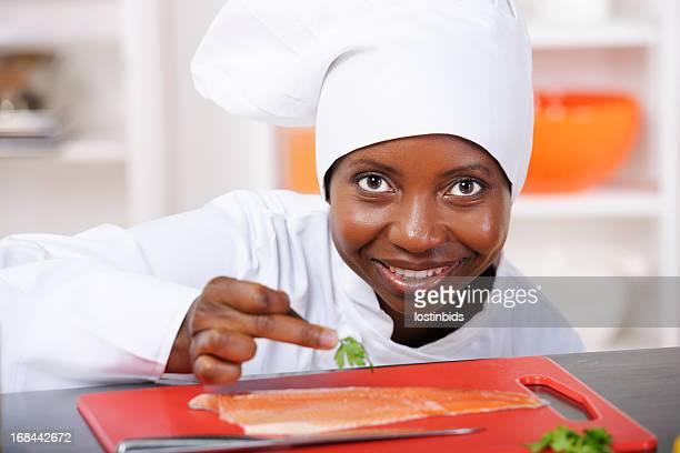 Portrait Of An African American Female Chef Preparing Fish