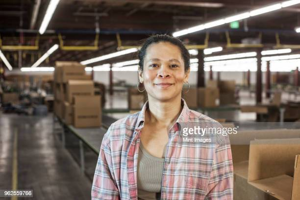 portrait of an african american female warehouse worker in a large distribution warehouse with products stored in cardboard boxes. - asian 50 to 55 years old woman stock photos and pictures