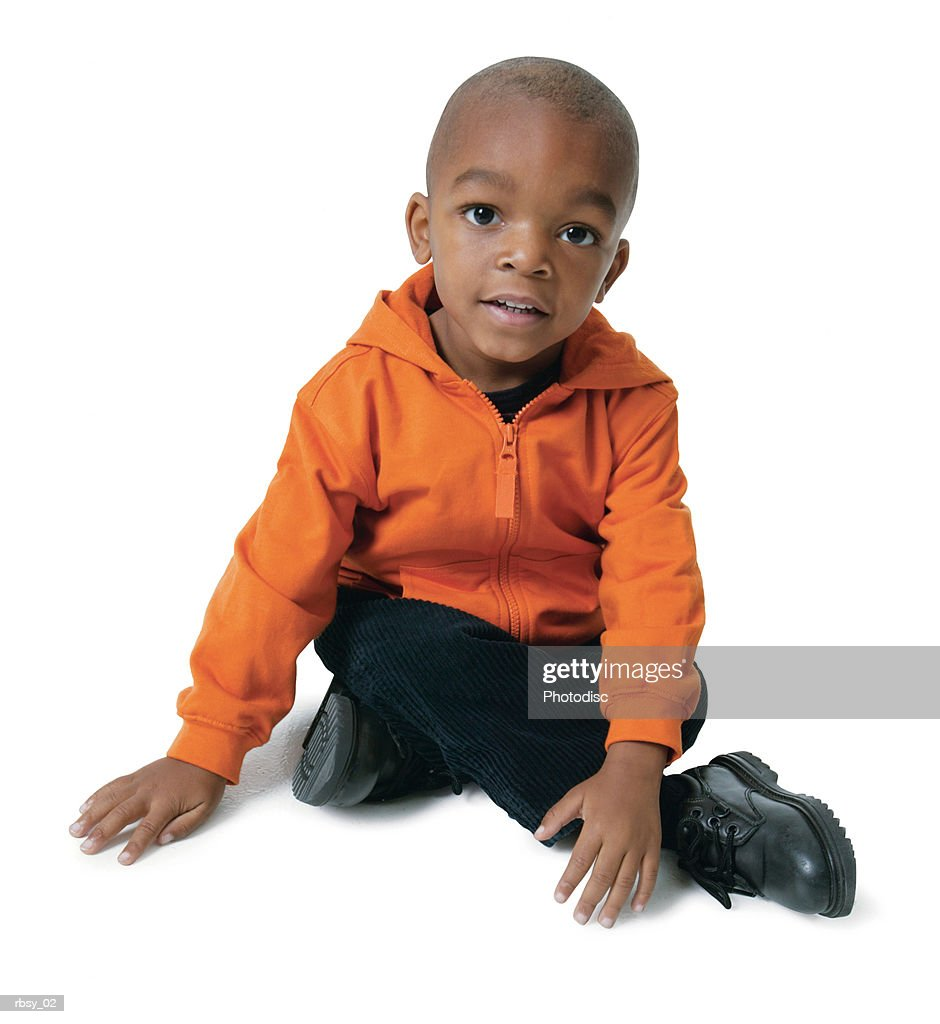 portrait of an african american male toddler in an orange shirt as he sits and smiles : Foto de stock