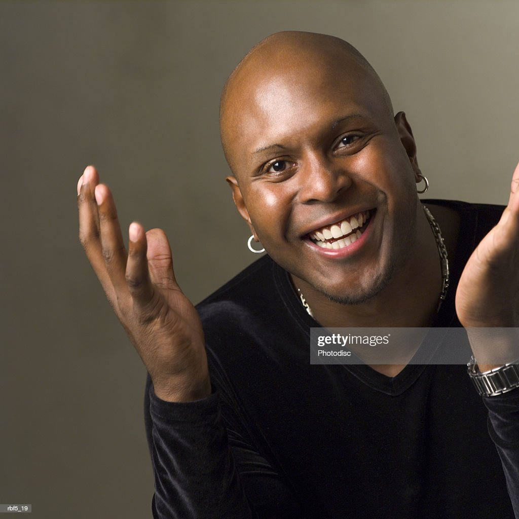 portrait of an african american man in a black shirt as he smiles and gestures with his hands : Stockfoto