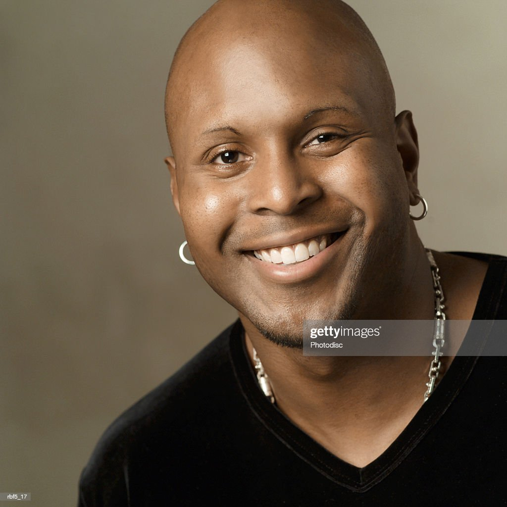 portrait of an african american man in a black shirt as he smiles into the camera : Stockfoto