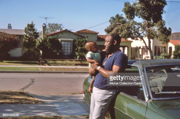 Portrait of an African American man smiling at an African American infant he holds in his arms July 1975 The man leans against a car parked in a...
