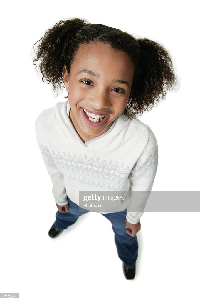 portrait of an african american teenage girl in a white sweater as she smiles up at the camera : Foto de stock