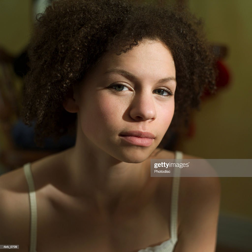 portrait of an african american teenage girl with as she looks seriously into the camera : Stockfoto