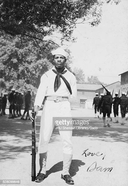 Portrait of an African American US Navy Sailor standing in front of two groups of sailors practicing in dark colored outfits he is wearing a light...