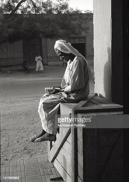 Portrait of an African man dressed in a tunic and turban photographed seated on a wooden packing case at the side of a road smiling as he reads a...