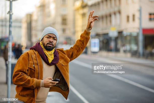 portrait of an african man who is standing in the city street and trying to catch a ride. - world sports championship stock pictures, royalty-free photos & images
