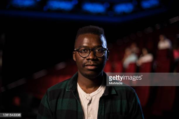 portrait of an african-american man at the cinema - film screening stock pictures, royalty-free photos & images