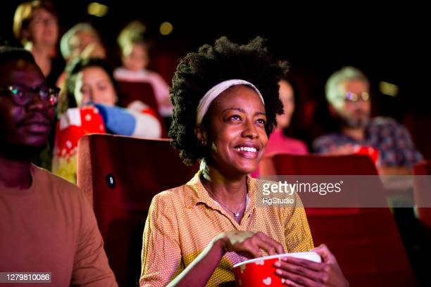 portrait of an african-american young woman enjoying with a friend at the cinema - film industry stock pictures, royalty-free photos & images
