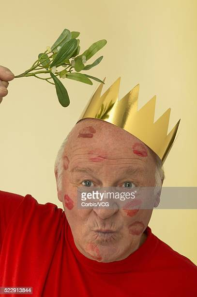 Portrait of an aging man covered in lipstick kisses holding some mistletoe over his head