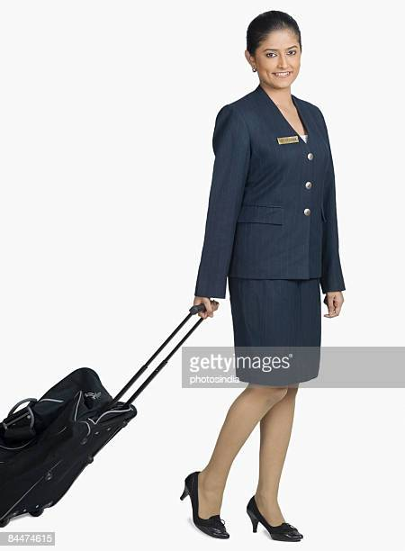 Portrait of an air hostess carrying her luggage