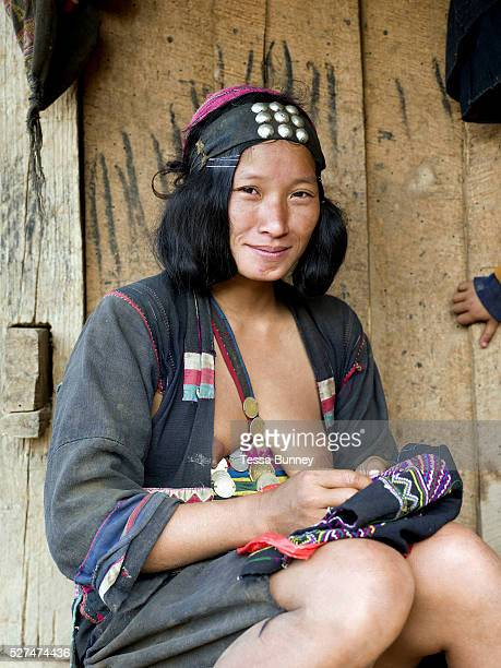 Portrait of an Akha Cherpia ethnic minority woman sewing traditional clothing outside her home in Ban Nam Hin village Phongsaly Province Lao PDR One...