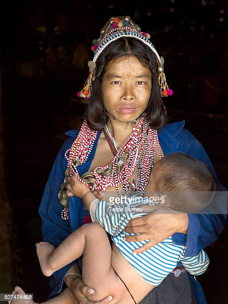 Portrait of an Akha Eupa ethnic minority woman breastfeeding her baby son in Ban Sa Nam Yang Pa village Phongsaly province Lao PDR One of the most...