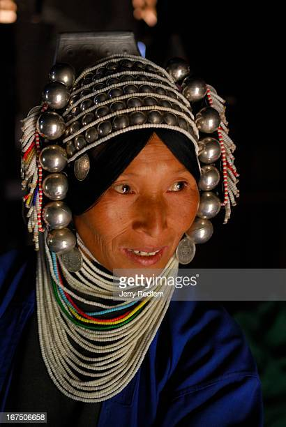 Portrait of an Akha woman wearing her traditional headdress and clothing in her home in rural Shan State Myanmar