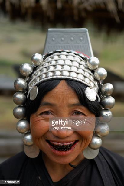 Portrait of an Akha woman wearing her traditional headdress and clothing in her farm fields in rural Shan State Myanmar Her teeth are stained black...