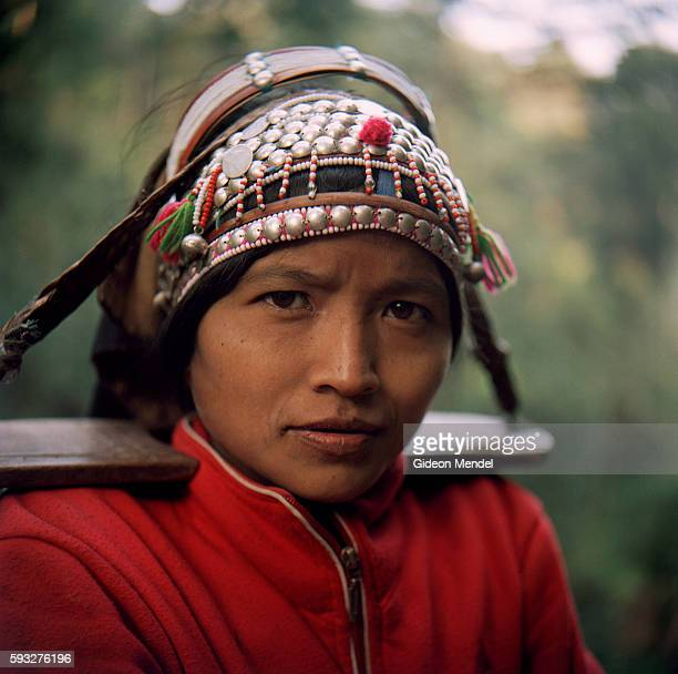 A portrait of an Akha woman wearing their intricately crafted traditional headress She was walking on the trail to in the Ban Nam Lai Akha village...