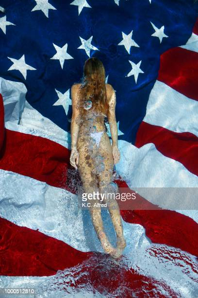 portrait of an all american girl floating in a swimming pool above american flag on a sunny day in san diego, california. - social awareness symbol stock photos and pictures
