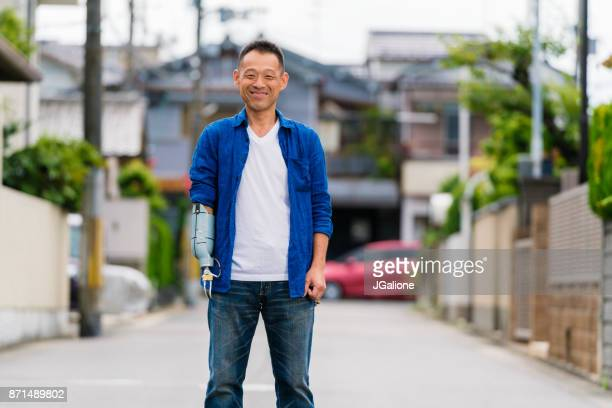 portrait of an amputee mid adult man stood outdoors - amputee stock pictures, royalty-free photos & images