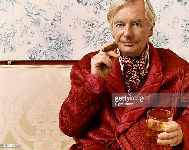 portrait of an aristocratic man in a smoking jacket sitting on a chaise longue holding a glass of whiskey and a cigar - smoking jacket stock photos and pictures